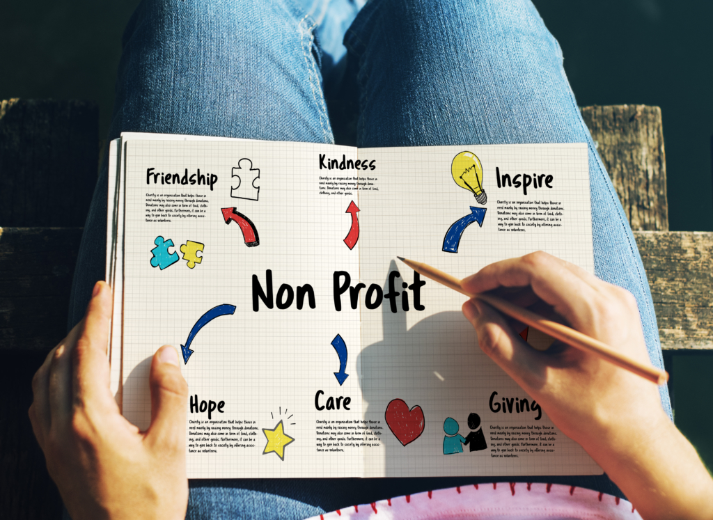 Person with a book on their lap that shows a diagram with the words Non-profit in the centre, with arrows out leading to attributes that read the words friendship, kindness, inspire, hope, care and giving